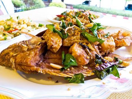 Fried mango fish  nilotica fish , topped with Thai herbs and nut photo