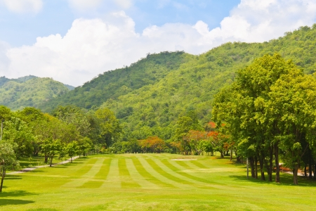 Golf fairway of a golf course, surrounded by bushes and trees, beside the mountain