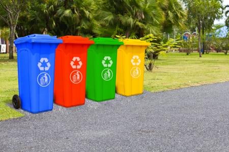 Vier kleuren vuilnisbakken vuilnisbak in het park naast het lopen weg Redactioneel