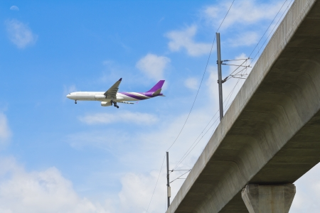 airplane take off: Two engines aircraft prepares for landing over skytrain railroad  airport link train , Bangkok, Thailand