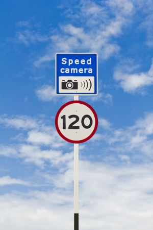 Speed limit and speed camera signpost, in English, blue sky background photo