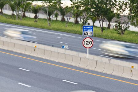 Speed limit  120 km hour  and speed camera signpost on motor way with cars in motion photo