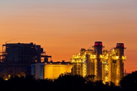 Gasturbine elektriciteitscentrale bij zonsondergang met oranje hemel