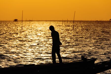 Silhouette of fisherman on his boat at sunset, Thailand photo