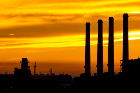 Silhouette of gas turbine electrical power plant at dusk photo