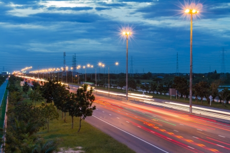 Traffic at dusk on motor way with light trails, Thailand 免版税图像