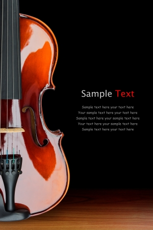 bout: Close up of shiny violin on wooden table, isolated on black background