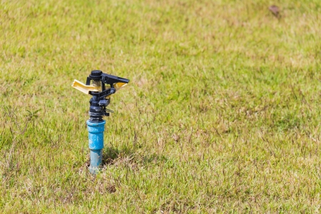 Unused automatic sprinkler head of watering system on the lawn 免版税图像