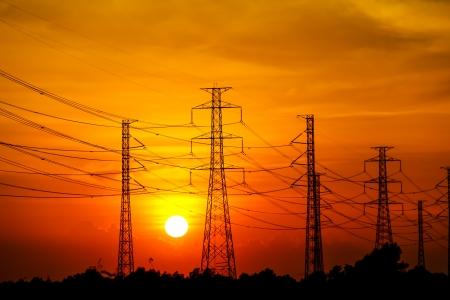 Silhouet van hoogspanning hoogspanningslijnen en pylonen bij zonsondergang, Thailand
