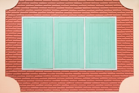 Teal rectangular wooden window on bare brick wall photo