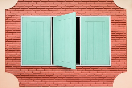 Teal rectangular wooden window on bare brick wall, one window is open photo