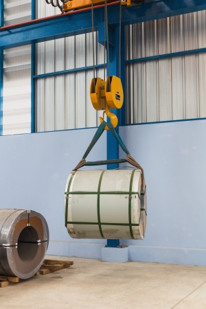Lifting steel coil by overhead crane, material handling photo