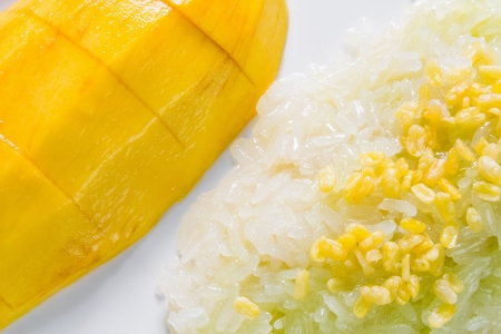 Ripe mango and sticky rice cooked with sweet coconut milk and topping with roast mung bean, Thai traditional dessert photo