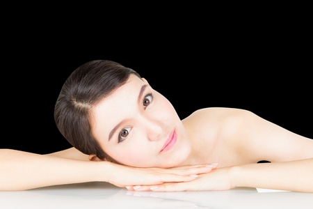 Beautiful young woman relaxes on table with exposed shoulder, isolated on black background photo