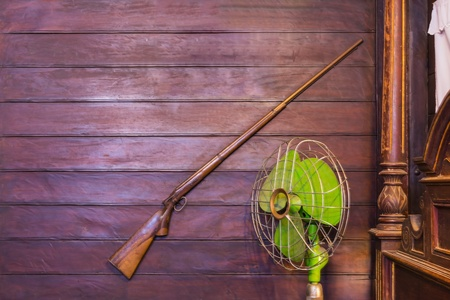 Old style room decoration with old rifle and old electric fan photo