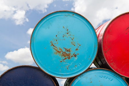litre: Stack of different color 200 litre metal oil or chemical barrels in storage area Stock Photo
