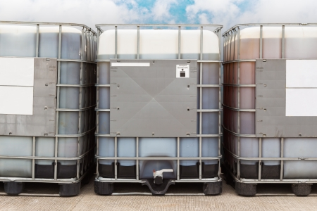 Bulk plastic oil containers with metallic cage in storage area 免版税图像