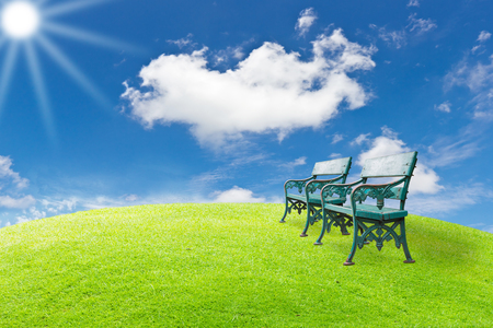 Old benches in green grass field with clear blue sky on sunny day photo