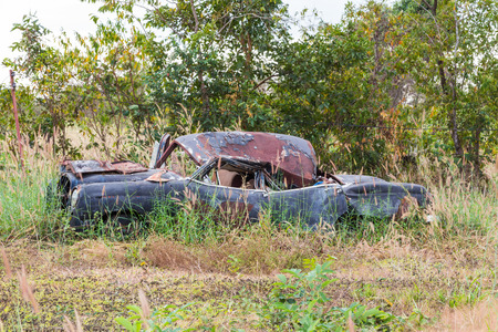 Abandoned wreck of old car in the field photo