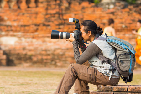 Tourist woman with backpack takes photo in Thai old temple