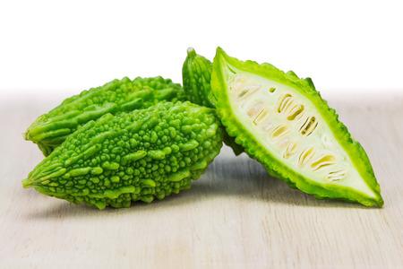 Close-up van kleine groene bittere meloen op houten hakblok Stockfoto