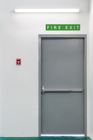 Fire exit steel door for evacuation in case of fire, with fire alarm pull switch on the wall near the door