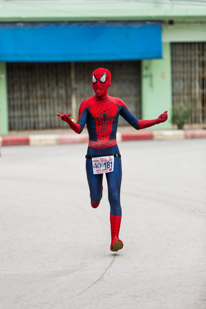 spiderman: CHONBURI, THAILAND - 20 JULY 2014 - Unidentified fancy athlete in spider-man suit run in twelfth Walk and Run Phanat Nikhom Supper Mini-marathon race at Phanat Nikhom district, Chonburi, Thailand