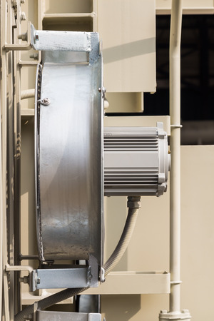 convection: Side view of electrical cooling fan attached to the radiator fin of the transformer, focusing on its motor