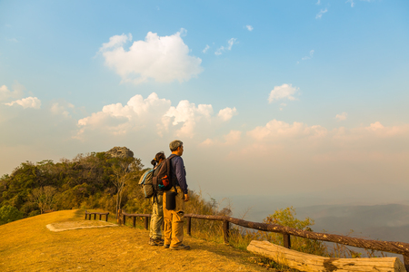 dao: Tourist man and woman stand on top of mountain at Doi Samer Dao, Thailand, evening sunlight