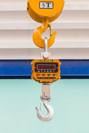 overhead crane: Industrial type 5000 kg digital weight scale hanging on hook of the crane