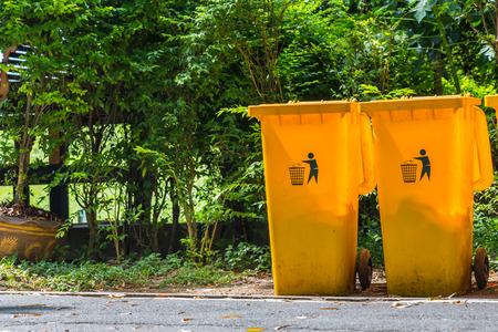 botes de basura: Botes de basura amarillas en la carretera en el parque