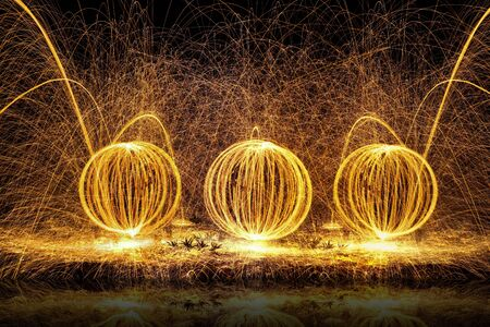 steel balls: Fire balls of spinning hot steel wool, with water reflection