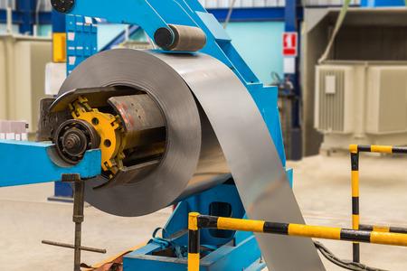 coil: Bobina de acero laminado en frío en decoiler de la máquina en la fabricación de carpintería metálica Foto de archivo
