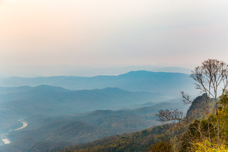 sunset tree: Tropical mountain ranges in the haze at dawn, northern Thailand Stock Photo