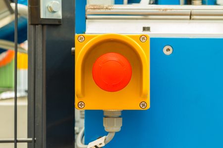safety device: Close up of emergency stop button switch, an electrical device for safety, installed on the machine
