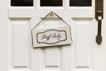 staff only: Staff only sign hangs on the wooden door