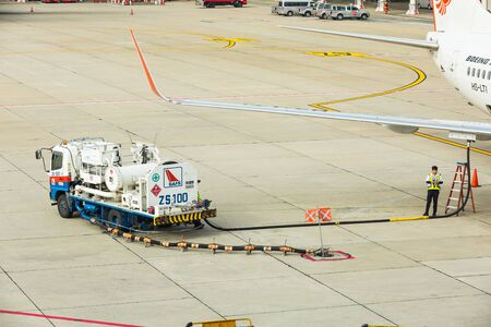 underwing: BANGKOK, THAILAND - 12 SEPTEMBER 2015 - Refuel truck with pressure apparatus and hose is used for underwing fueling also called single-point refueling or pressure refueling to Boeing 737 aircraft at Don Mueang International Airport, Bangkok, Thailand.
