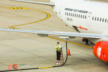 underwing: BANGKOK, THAILAND - 12 SEPTEMBER 2015 - Unidentified engineering worker works on underwing fueling also called single-point refueling or pressure refueling to Boeing 737 aircraft at Don Mueang International Airport, Bangkok, Thailand.
