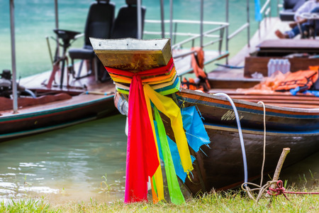 thani: Traditional Thai longtail boats moor at shore to wait for their tourists in Cheow Lan reservoir in Surat Thani province, Thailand, focusing on its bow Stock Photo