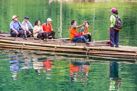 thani: SURAT THANI, THAILAND - 12 SEPTEMBER 2015 - Unidentified guide and tourists travel on the bamboo raft for sightseeing in Cheow Lan reservoir in Surat Thani province, Thailand. Editorial