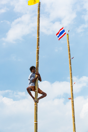 racing festival: CHONBURI, THAILAND - 26 OCTOBER 2015 - Unidentified participant climbs up the oiled bamboo pillar in the 144th Chonburi Buffalo Racing Festival on October 26, 2015 in Chonburi, Thailand.