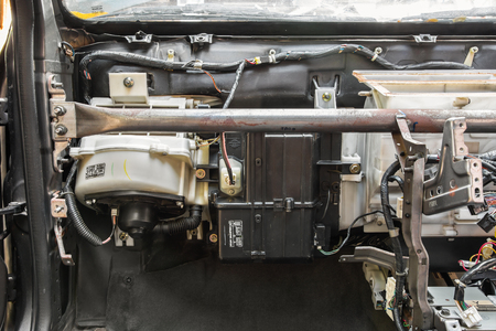 beneath: CHONBURI, THAILAND - 23 OCTOBER 2015 - Air conditioning parts evaporator coil unit beneath the front console of Nissan Primera P11 car. The front console has been removed for repairing and cleaning purpose. Editorial