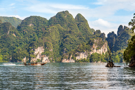 surat: SURAT THANI, THAILAND - 13 SEPTEMBER 2015 - Unidentified tourists travel on traditional Thai longtail boat for sightseeing in Cheow Lan reservoir in Surat Thani province, Thailand.