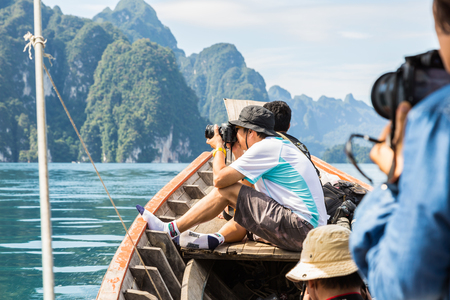 surat: SURAT THANI, THAILAND - 13 SEPTEMBER 2015 - Unidentified tourists take photo from boat while travel on traditional Thai longtail boat in Cheow Lan reservoir in Surat Thani province, Thailand. Editorial