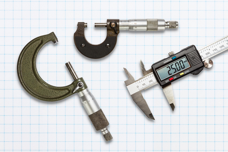 micrometers: Micrometers and digital vernier calipers, isolated on graph paper with clipping path