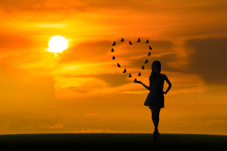 Love concept, full length of woman posing standing with butterflies flying in heart shape at sunset