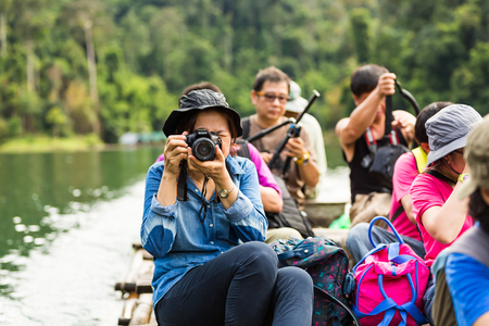 surat: SURAT THANI, THAILAND - 12 SEPTEMBER 2015 - Unidentified tourists take photo from bamboo raft while travel on bamboo raft in Cheow Lan reservoir in Surat Thani province, Thailand. Editorial
