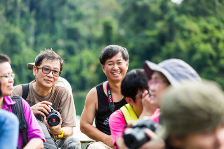 thani: SURAT THANI, THAILAND - 12 SEPTEMBER 2015 - Unidentified tourists take photo and feel happy while travel on bamboo raft in Cheow Lan reservoir in Surat Thani province, Thailand.