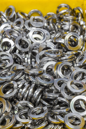 stainless: Close up of stainless steel spring washers in yellow plastic tray in the factory, a shop floor item Stock Photo
