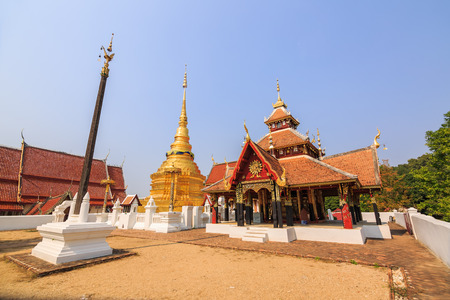 multi layered: Wide angle view of multi layered roof and cruciform shaped pavilion Viharn Phra Chao Phan Ong and golden Buddhist pagoda
